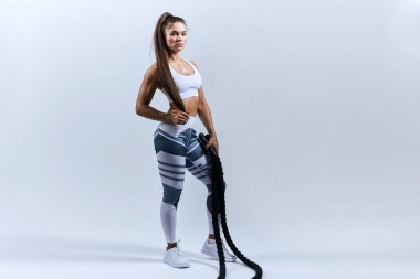 sexy tired sportswoman after battle rope workouts on white background.
