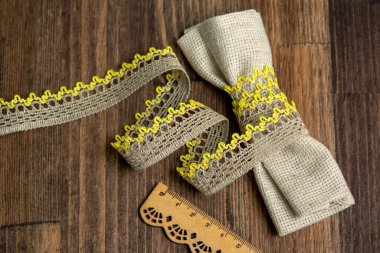 knitted yellow openwork linen ribbon tapes in rural style of rustics cotton eco natural on wood ground