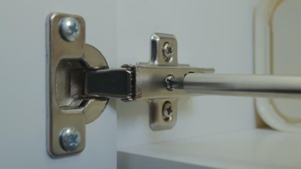 dreht der Meister die Stellschraube des Scharniers der Schranktür in der Küche. Montage und Anpassung von Türen für Küchenschränke. Nahaufnahme. 4K