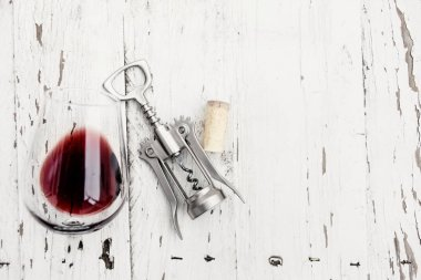 Top view of red wine in glass, wine cork and corkscrew on white wooden table stock vector