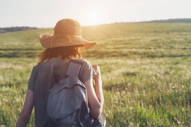 young woman wearing linen dress and straw hat with backpack enjoying nature an walking outside, traveling