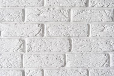 Decorative rough white brick wall background closeup