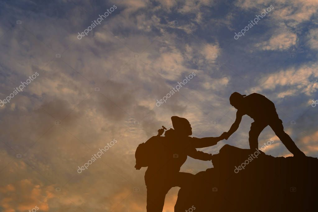 Two friends helping each other trying to reach top of mountains during wonderful summer sunset.