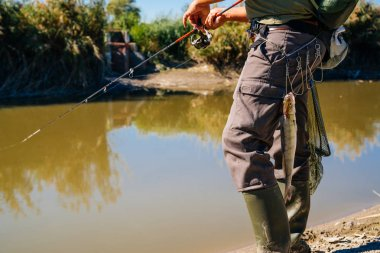 Fish hanging on Fisherman's belt with fishing rod