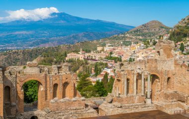 Ruins of the Ancient Greek Theater in Taormina with the Etna volcano in the background. Province of Messina, Sicily, southern Italy.