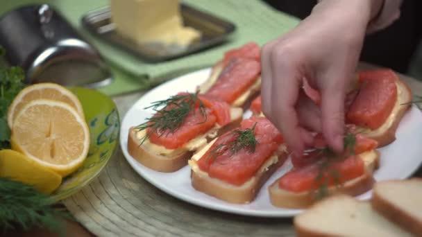 Koch legt grüne Koriander und Dill auf leckere und köstliche Sandwiches mit rotem Fisch Lachsforelle, Nahaufnahme, Zeitraffer, 5x Geschwindigkeit, gesundes Essen, kochen, kochen