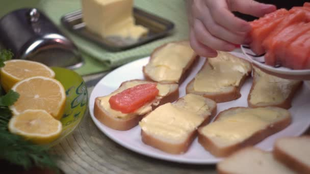 Girl chef puts red fish salmon trout on bread with butter, making red fish sandwiches, close-up, healthy food, cook,