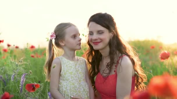 Daughter, 6 year old kisses and hugs happy mother in the meadow with poppies and flowers. Happy and touching moments of love mom and daughter. Mothers day