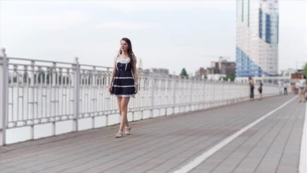 Az Európai nő barna hajú nő, hosszú haja a kék fehér rövid sundress lassan sétál végig a rakparton a folyó, lassított