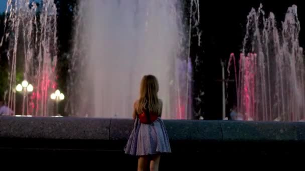 Dětská Evropská dívka v modrých šatech s batohu v podobě Beruška ve večerních hodinách obdivuje fontánu, pohled zezadu, pomalý pohyb, jiskřící světla