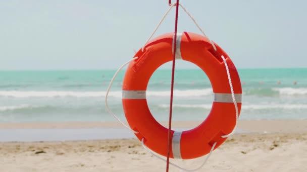 Roter orangefarbener Rettungsring an einem Sandstrand im Sommer in der Badesaison am Meer, Nahaufnahme
