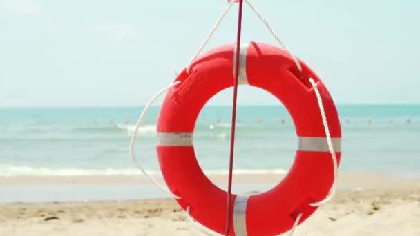 Roter orangefarbener Rettungsring am Sandstrand im Sommer in der Badesaison am Meer, Nahaufnahme, Zeitlupe