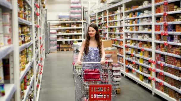 Attractive European woman walking with big red cart through supermarket, grocery store and choose products, front view, slow motion, shopping