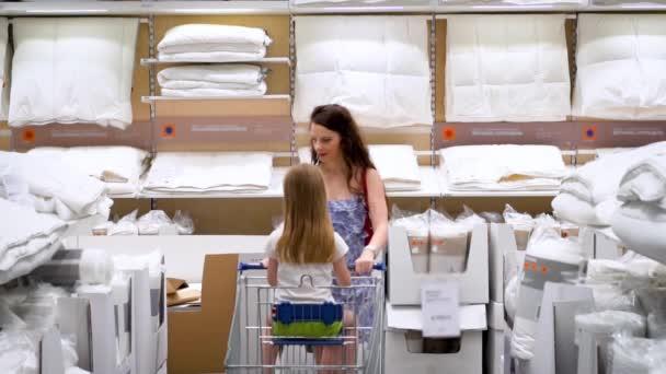 Matka a dcera jezdí v supermarketu s velkým vozíkem, nakupují lůžkoviny a mají přikrývku, polštář, pohled zepředu, pomalý pohyb, nakupování