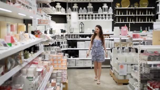 Atraktivní Evropská žena s dlouhými hnědými vlasy v krátkých opalových šatech kolem domácího obchodu, supermarketu, pomalého pohybu