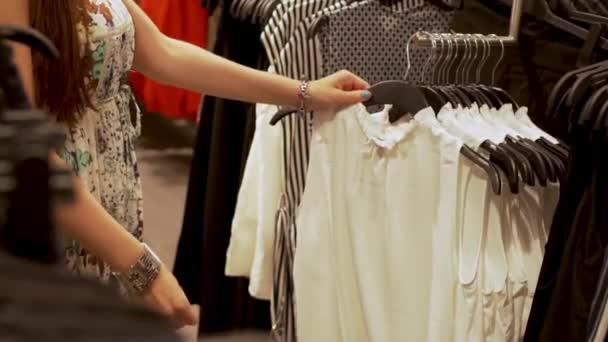 Mädchen Shopaholic wählt eine modische weiße Bluse Kleidung in einem Bekleidungsgeschäft Mode Boutique Einkaufszentrum Nahaufnahme, das Konzept des Einkaufs und Verkaufs