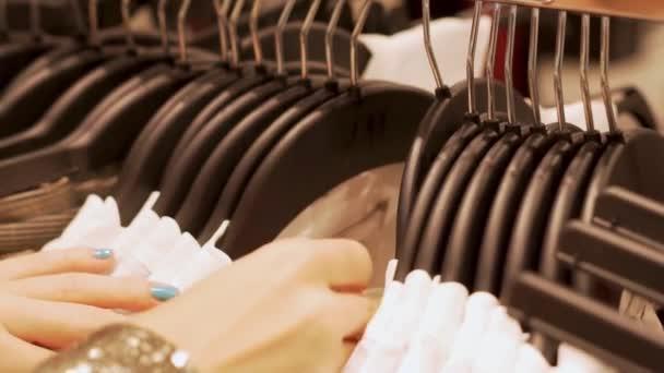 Blízkka dívky, která se rozjíždí a dívá se na oděv s velikostí a cenou v módním obchodě na věšáky na šaty, v blízkosti věšáku na šaty, konceptu nákupu a prodeje