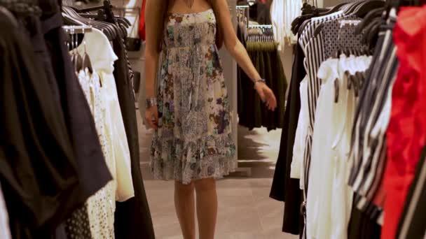 Blízko dívky, která chodí po řadě s racky a věšáky na šaty a vede si ruce nad šaty v módním obchodě s Boutique, koncept nákupu a prodeje