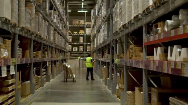 Nagy hatalmas tároló területek áruk, raktár munkás néz artkul árut egy okostelefon, és úgy az árut a polcról, csúsztatva a kamerát a bal