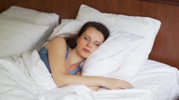 Közeli fel az Európai lány édesen alszik az ő oldalán ölelgetés egy párnát, reggel az ágyban az ő hálószoba elülső nézet lassított