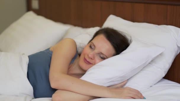 Közeli fel a nő alszik édesen felébred, és boldog nyújtás, fehér ágyban aludni a hálószobában, lassított