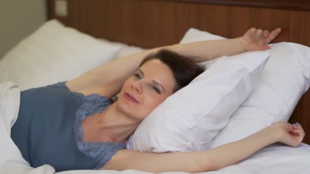 Close-up of young woman wakes up and enjoys stretching in white pastel in bed in bedroom, slow motion