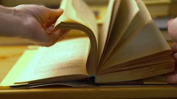 Detailní záběr ženských rukou obracejících stránky staré knihy. Koncepce čtení, vzdělávání a učení.