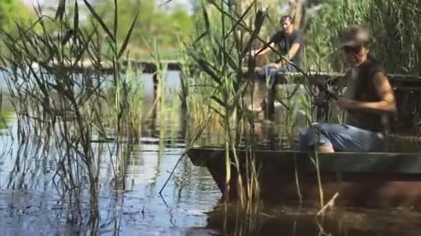 Mladá rybář loví na lesním jezeře a drží rybářskou tyč ve svitku.