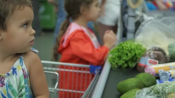 Malá holčička v supermarketu v nákupním košíku