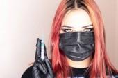 junges Mädchen in medizinischer Maske, Handschuhen und Spritze. Mode für medizinische Dressings unter jungen Menschen. Das Konzept der kosmetischen Dienstleistungen, Injektionen, Botox, moderne Mode, um medizinische Masken zu tragen