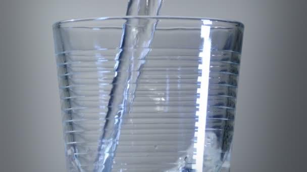 Padající voda ve sklenici. Zobrazení vody, která se nachází v blízkosti skleněného skla