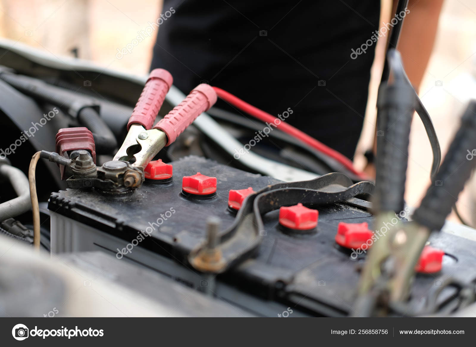 Mechanic use jumper cables to charge dead car battery
