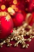 Fotografia Ornamenti di natale rosse e dorate su fondo luminoso del bokeh