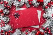 Veselé Vánoce a šťastný svátky blahopřání, rám, banner. Nový rok. Noel. Vánoční ozdoby, obálka kryt a jedle na červeném pozadí pohledu shora. Zimní dovolená téma. Rozložení bytu