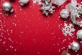 Fotografie Veselé Vánoce a šťastný svátky blahopřání, rám, banner. Nový rok. Noel. Pohled shora na vánoční bílé a stříbrné ozdoby na červeném pozadí. Zimní dovolená téma. Rozložení bytu
