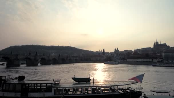 Boats sail the Vltava river in Prague with the Castle in the background, Czech Republic during a sunset in April - 2019
