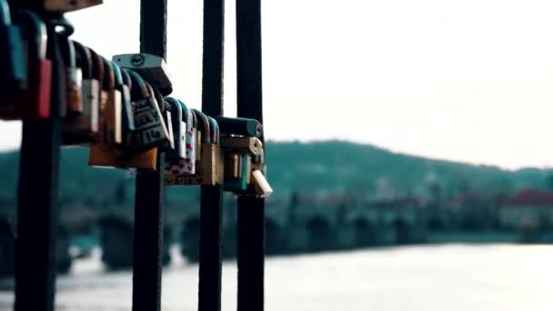 Zamknout zámky visí od zábradlí vedle Karlova mostu a představuje lásku, přátelství a romantiku