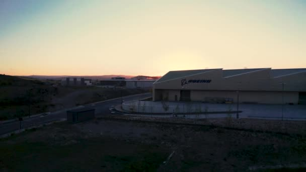 Aerial footage of the Boeing UK aircraft factory infront of a beautiful sunset
