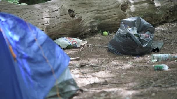 Aldershot, Velká Británie - 7. června 2020: Táborníci nechávají láhve alkoholu v igelitových sáčcích a stanech po noci strávené pařením v lese.