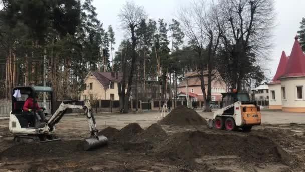 Dva traktory v provozu. Rypadlo kope na zem. Dělníci pracují na těžkých strojů. Stavitelé úroveň půdy pro položení dlažební desky.