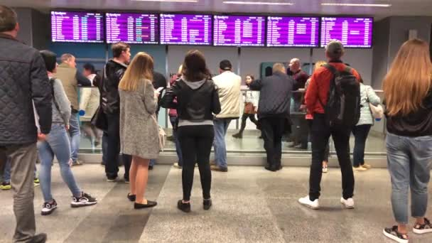 People stand at the airport and wait for the arrival of the aircraft. In the airport lounge, many people are standing and looking at the bulletin board. Boryspil Airport, Kiev, May 9, 2019
