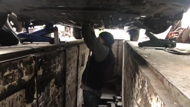 Master repairs the car. The mechanic makes the diagnosis of the car. Repair shop in Irpen, Kiev region, May 16, 2019.