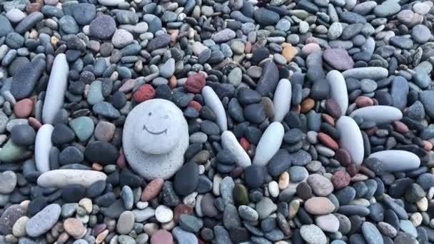 Nápis na kamenech je láska. Bílé oblázky jsou rozloženy slovem láska na pozadí mořských kamenů na pobřeží. Obličejová kresba s úsměvem na bílém kameni.