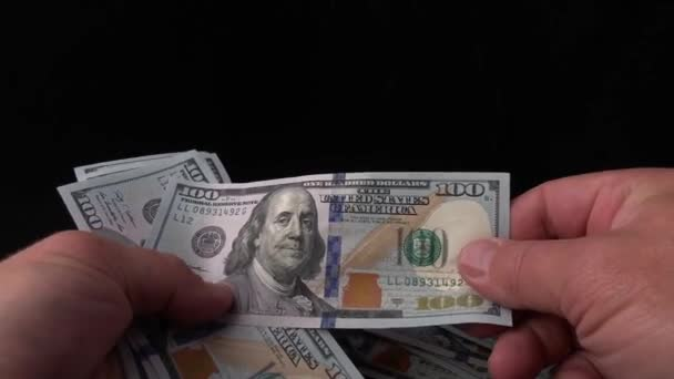 Man counts dollars on a black background. In the hands of a man a bundle of American money. Checking one hundred dollar bills for a fake. Concept: wealth, enrichment, verification of fake money.
