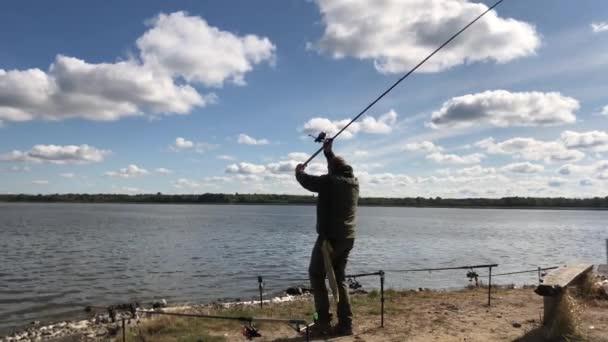 Rybář se roztočí v jezeře. U řeky rybaří nějaký muž. Muž s prutem chytá ryby v rybníce.