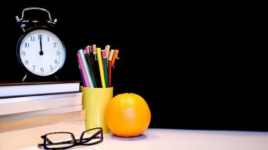 Back to school background with alarm clock, books, glasses, orange and pencils.