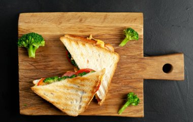 Fresh grilled sandwiches with ham, fresh broccoli and cheese on wooden chopping board