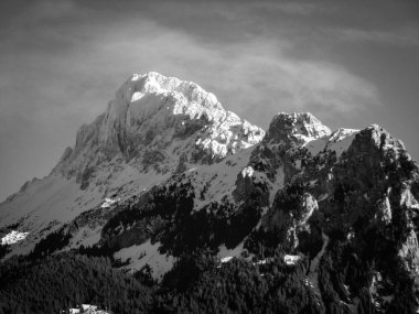 Black and white mountain landscape photography in the french Alps, snow and forest, sunlight in the pic