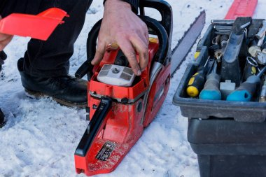 Repair and maintenance of a red chainsaw, close-up