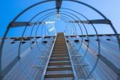 Függőleges fém lépcsőház a tető a hangár. A lépcsőházat védőkerettel veszi körül